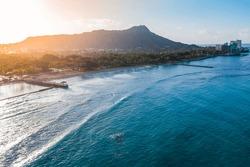 Diamond Head Mountain and Waikiki Queens Beach during sunrise. Palms on the beach with light effect. Oahu Island, Hawaii