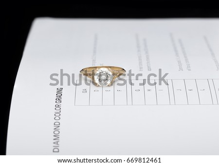 Diamond on a ring setting on color grading scale book of GIA