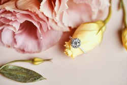 Diamond Ring and Pink Flower Background. Close up of an elegant engagement diamond ring.
