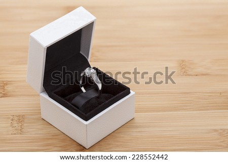 Diamond ring in white box on a wooden background