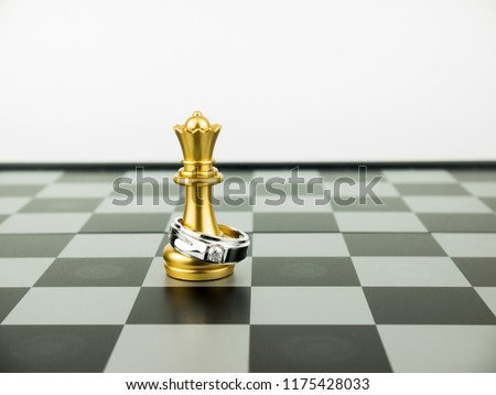 Diamond ring with king chess piece on the board, Wedding Concept.