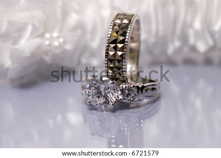 Diamond ring with wedding band set against a white garter and reflective surface - stock photo