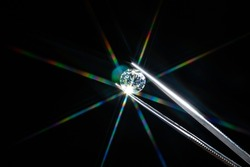 Diamond selective focus held in metal jeweller tweezers, brilliant stone cut with star shape light ray burst, starburst or sunbeam. Inspection of polish quality and contamination. Carbon material.