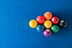 diamond shape of 9-ball pool balls placed in rack position on blue felt table, top view, copy space