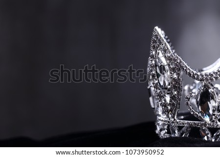 Diamond Silver Crown for Miss Pageant Beauty Contest, Crystal Tiara jewelry decorated gems stone and abstract dark background on black velvet fabric cloth, Macro photography copy space for text logo #1073950952