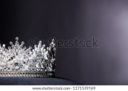 Diamond Silver Crown for Miss Pageant Beauty Contest, Crystal Tiara jewelry decorated gems stone and abstract dark background on black velvet fabric cloth, Macro photography copy space for text logo #1171539169