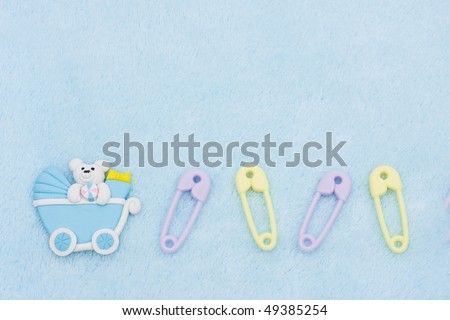 Diaper pins and a baby carriage on a blue textured background, baby border
