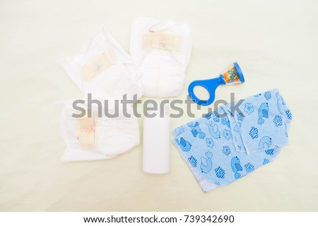 diapers, toy, clothes, powder in the background. Newborn accessories on a green background.