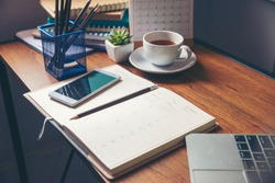 Diary and notebook for Planner to plan agenda, reminder, timetable, daily appointment, management on table. Calender, laptop, smartphone and cup of coffee place on office desk. work online at home.