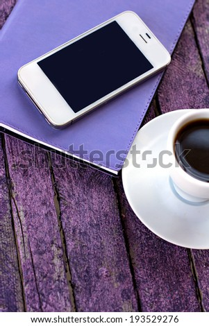 diary, mobile phone and a cup of coffee on the old desk