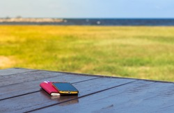 Diary,note book papers and smartphone on wooden at beach background,sea