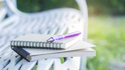 Diary of memories. Notebook and pen on steel benches in the park.