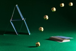 dice and playing cards on green table