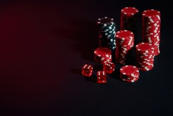 Dice and red and black chips on dark background