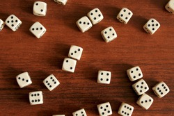 Dice are scattered on a wooden table. Cubes lie in random order. Slight blur.
