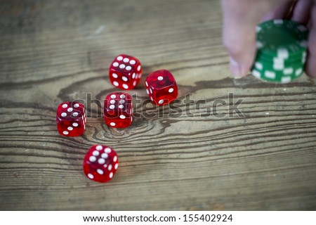 dice, chips in the hand and wooden table