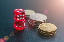 Dice, coins and chips of different denominations in a casino in light reflections