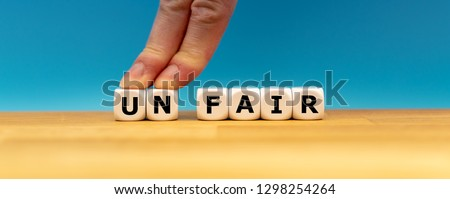 """Dice form the word """"UNFAIR"""" while two fingers push the letters """"UN"""" away in order to change the word to """"FAIR""""."""