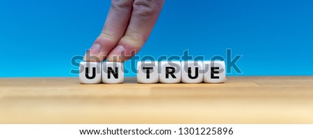 """Dice form the word """"UNTRUE"""" while two fingers push the letters """"UN"""" away in order to change the word to """"TRUE""""."""