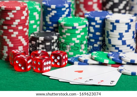 dice, four aces and colorful poker chips on a green table