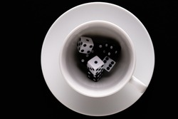 dice in a coffee Cup on a black background
