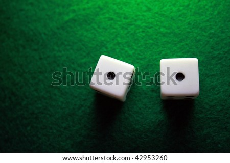 Dice over a green table showing snake eyes