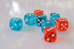 Dice rolls on the white table. Stuff for playing boardgame, casino or other recreation. Transparent dices for game play