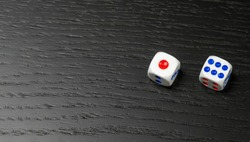 Dice with blue and red dots on black background with copy space