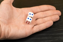 Dice with blue dots in a man's hand close up on a black background
