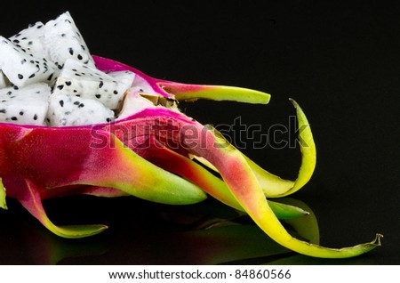 Diced dragon fruit pieces in the shell next to a whole fruit