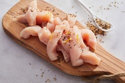 Diced fresh raw chicken breast cut in strips for a goulash or stir fry seasoned with spice rub heaped on a wooden chopping board on white marble