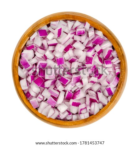 Diced red onions in wooden bowl. Cut cubes of onion cultivar Allium cepa, with purplish red skin and white flesh tinged with red. Closeup, from above, on white background, isolated, macro food photo. Stockfoto ©