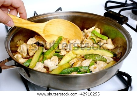 diced white chicken meat and fresh zucchini strips being sauteed in a frying pan