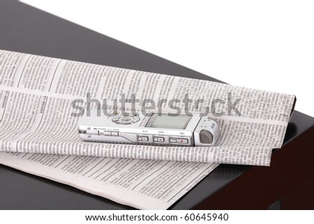Dictaphone and the newspaper on black table isolated on white background
