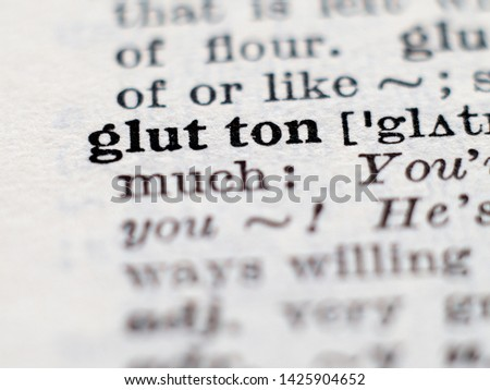 Dictionary definition of word glutton. Selective focus.