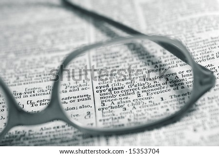 "Dictionary page focused on the word ""eyeglass"" through prescription eyeglasses."