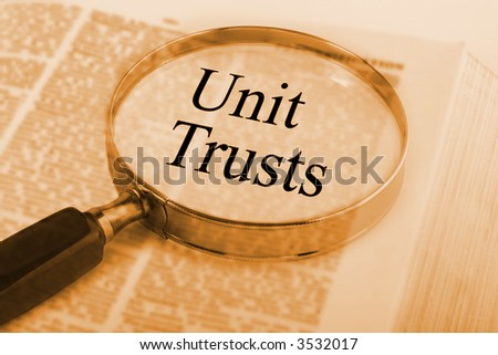 Dictionary with magnifying glass emphasising the words Unit Trusts. SEe others from this series in our portfolio.