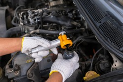 Diesel engine during service, or maintenance at the garage. Technical wear a glove and open the suction tube to analyze oil. Design of the old engine. Service, repair, and analysis concept