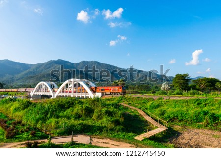 Diesel train in the middle of ancient white railway bridge across the river.Tha Chom Phu,White railway bridge tourist attraction on the northern Thailand railway.        #1212745450