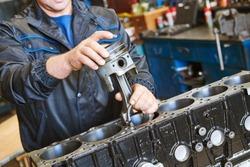 diesel truck engine repair service. Automobile mechanic installing piston into engine