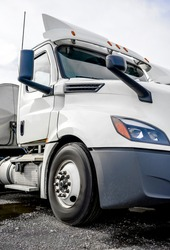 Diesel white big rig day cab semi truck with aerodynamic roof spoiler and stainless steel tank semi trailer standing on the warehouse parking lot waiting for the next load for timely delivery
