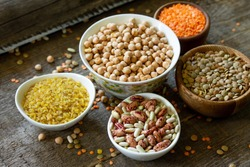 Diet and healthy eating concept, vegan protein source. Raw of legumes (chickpeas, red lentils, canadian lentils, beans, bulgur) on wooden table.