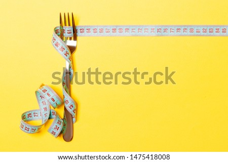 Diet and healthy eating concept with fork and measuring tape on yellow background. Top view of weightloss.