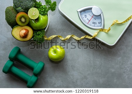 Diet and Healthy life loss weight Concept. Organic Green apple and Weight scale measure tap with vegan vegetable and sport equipment for body women diet slimming fit.  Top view and copy space.