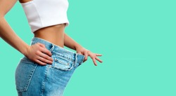 Diet concept and weight loss. Woman in oversize jeans on pastel green background