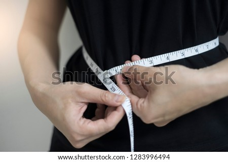 Diet concept close up women measuring waist circumference.