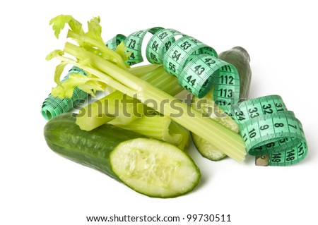 diet concept. cucumbers and celery green with measure tape