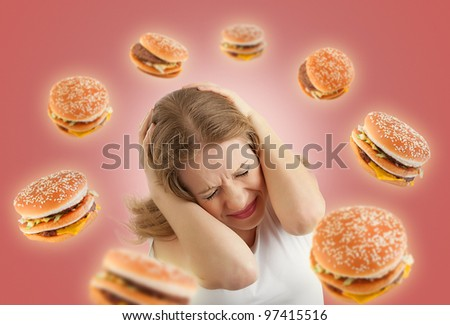 diet concept. frightened girl in the stress and flying around the burgers on a red background