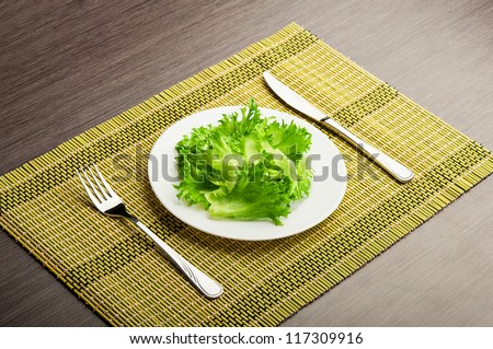 diet concept. green leaf lettuce on a plate with a fork and knife