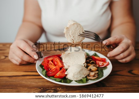 Diet concept, healthy lifestyle, low calorie food, low carb diet. Fat woman eating baked chicken breasts with salad, close up